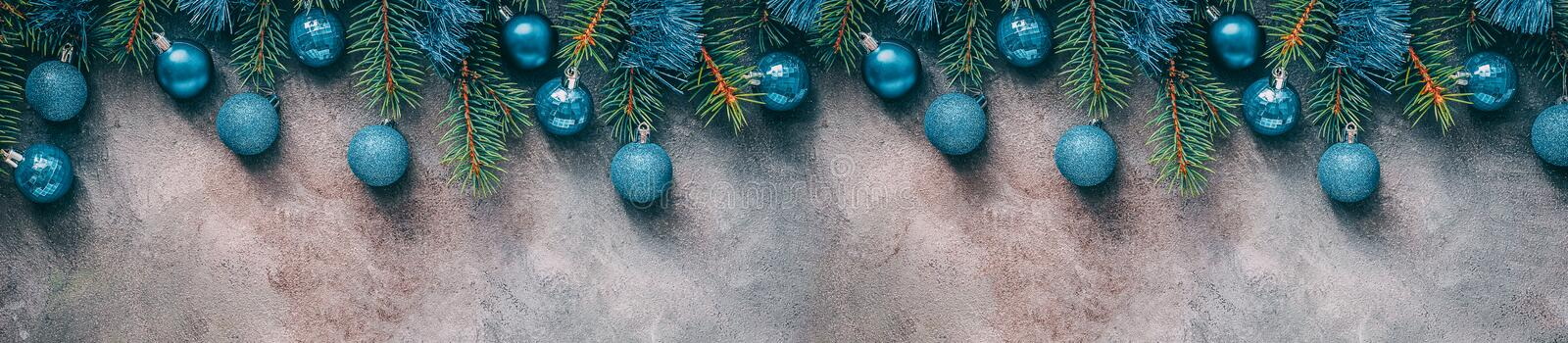 Beautiful Christmas border, fir branches decorated blue balls and tinsel on a dark textured rustic background. Top view, flat lay royalty free stock images