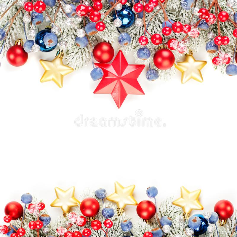 Beautiful Christmas card background. Colorful winter border with green Xmas tree twig, holly berries and red glass baubles. Isolated on white stock images