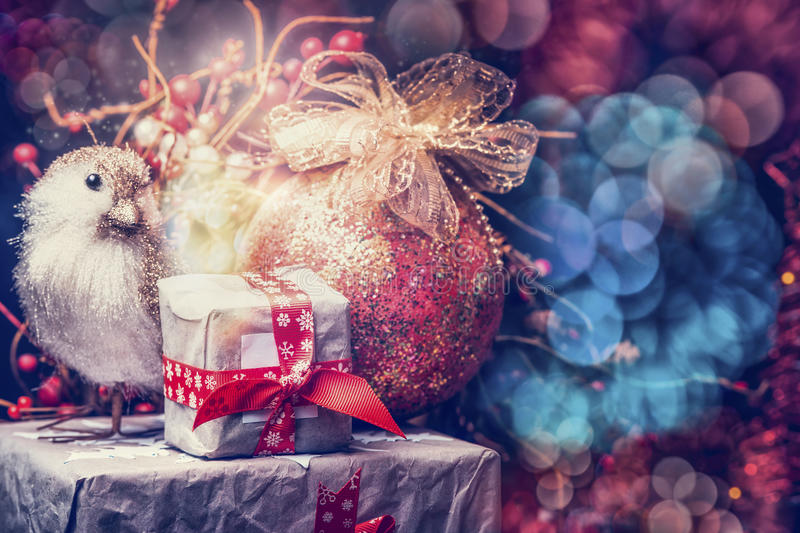 Beautiful Christmas card with festive bokeh lighting, gifts, red bow knot bird and ball, retro royalty free stock photography