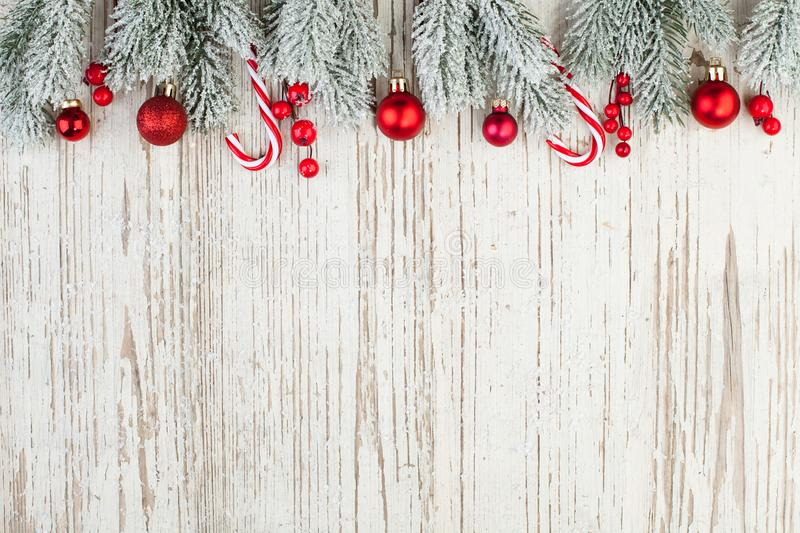 Beautiful Christmas composition border on white wooden background. Red holly berries, baubles and green fir branch. Minimal Xmas. Flat lay top view on wood royalty free stock photography