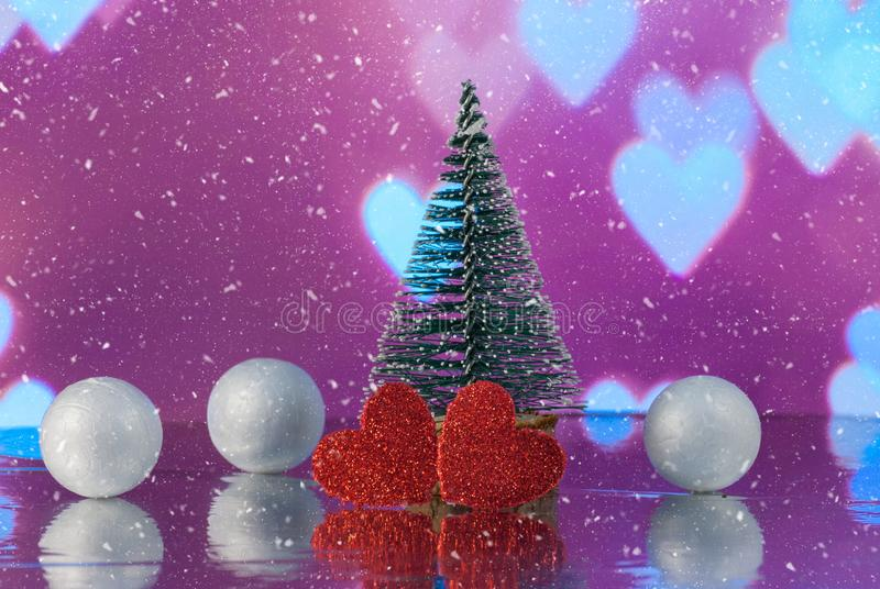 Christmas composition with Christmas tree, Hearts and decorative snowballs against holiday lights background. Beautiful Christmas composition with Christmas tree stock image
