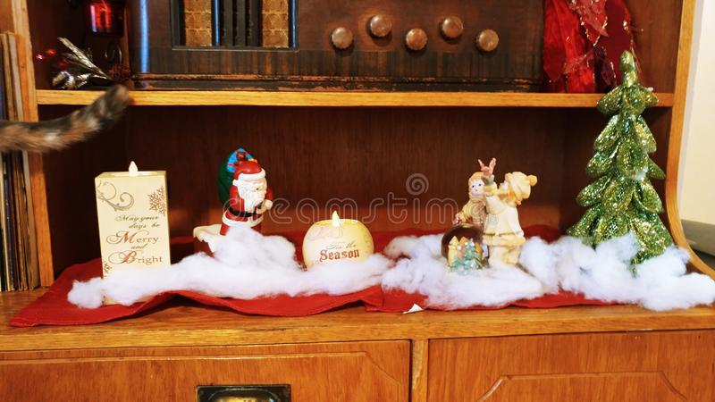Beautiful Christmas decorations and candles on brown shelf royalty free stock images