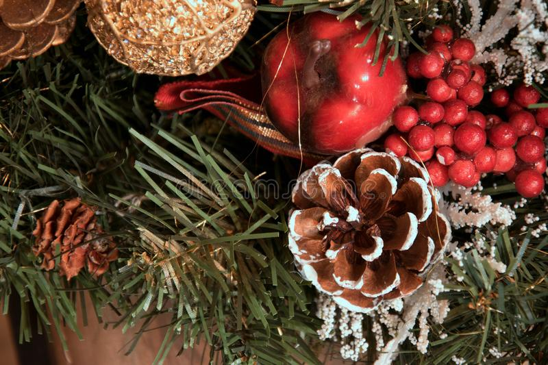 Beautiful Christmas decorations: a cone with snow, a red apple, a golden cone and a golden ball stock image