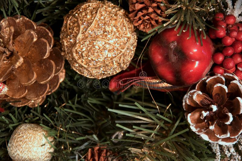 Beautiful Christmas decorations: a cone with snow, a red apple, a golden cone and a golden ball. A red curler, lie on the fir trees. Christmas wreath royalty free stock photos