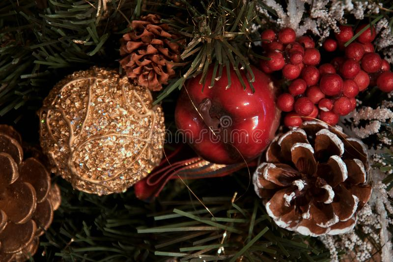 Beautiful Christmas decorations: a cone with snow, a red apple, a golden cone and a golden ball, a red curler, stock photography