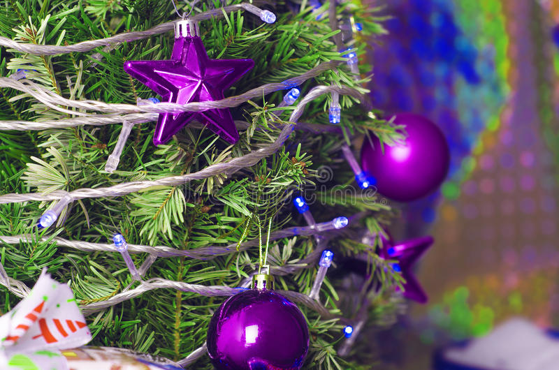 Beautiful Christmas decorations. Purple toys hang on the Christmas tree and the presents are near stock image