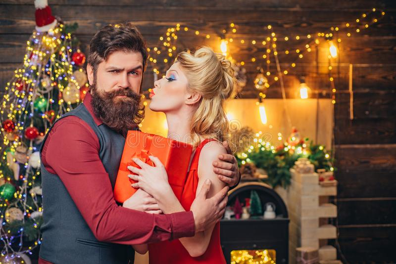 Beautiful Christmas family couple smiling with gift - wish you Happy New Year. Young Christmas fashion couple. Funny. Couple with colorful make-up and retro stock image