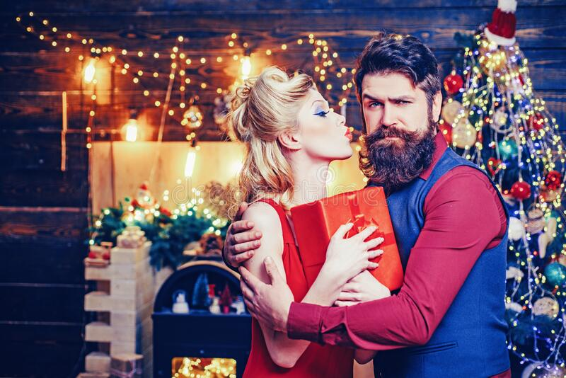 Beautiful Christmas family couple smiling with gift - wish you Happy New Year. Young Christmas fashion couple. Funny stock photo