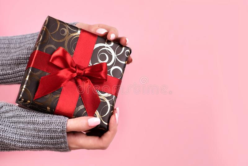 Beautiful Christmas gift with a red bow, in the hands of a young girl. Red sweater, Christmas balls and lights royalty free stock photos