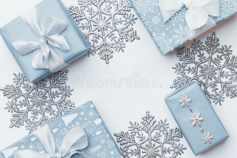 Beautiful christmas gifts and silver snowflakes isolated on white background. Pastel blue colored wrapped xmas boxes. royalty free stock image
