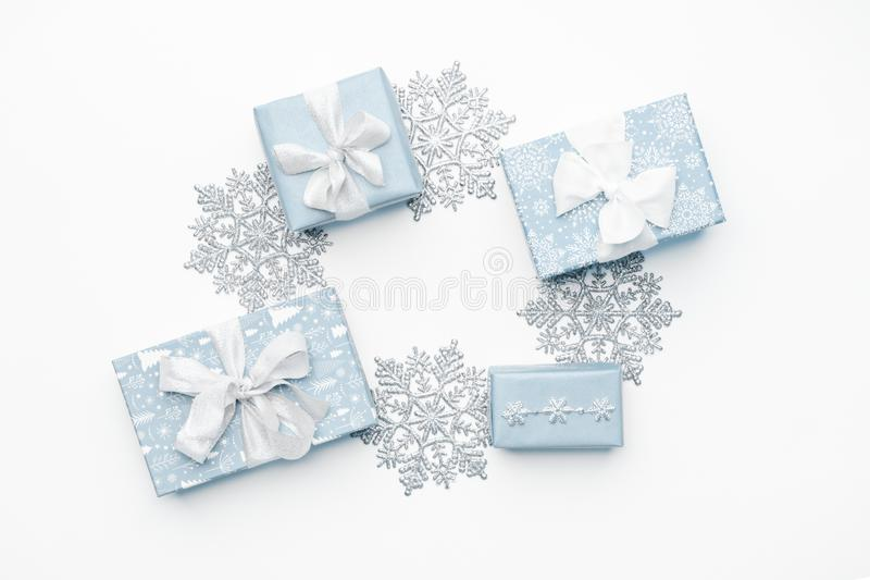 Beautiful christmas gifts and silver snowflakes isolated on white background. Pastel blue colored wrapped xmas boxes. royalty free stock photography