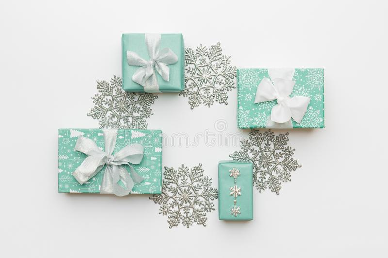 Beautiful christmas gifts and silver snowflakes isolated on white background. Turquoise colored wrapped xmas boxes. Gift wrapping concept royalty free stock photography