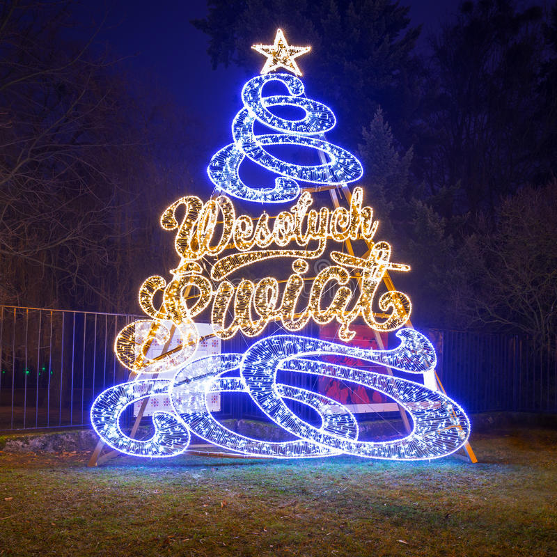 Beautiful Christmas illumination at the park. Beautiful Christmas tree illumination at the park with Wesolych Swiat Polish: Merry Christmas sign, Gdansk, Poland royalty free stock images