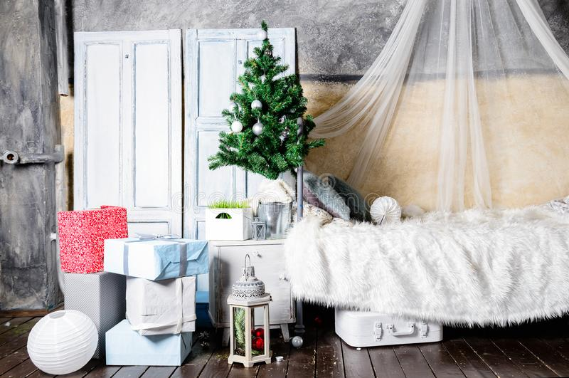 Beautiful Christmas interior design. Room decorated with Christmas tree, gifts, different boxes and comfortable sofa. Concept royalty free stock photography