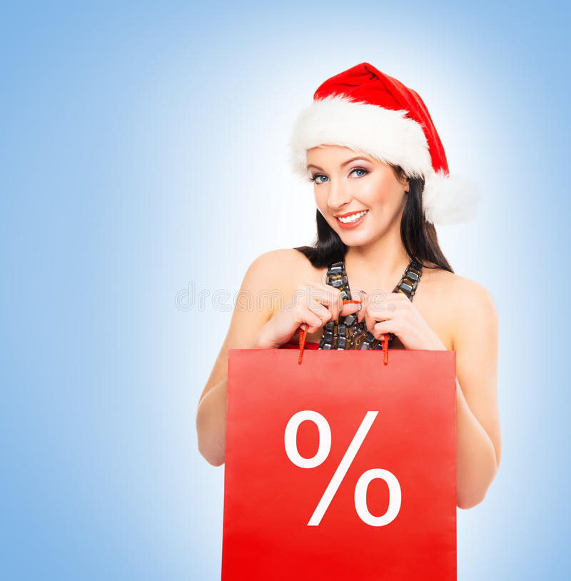 Beautiful Christmas shopper girl on a light blue background stock photo