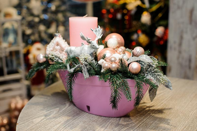 Beautiful Christmas table decorative composition with candle, toy deer, glass balls and fir tree in pink vase royalty free stock images