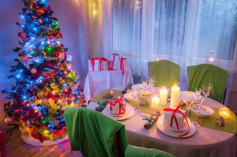 Beautiful Christmas table setting with Christmas tree and gifts royalty free stock image