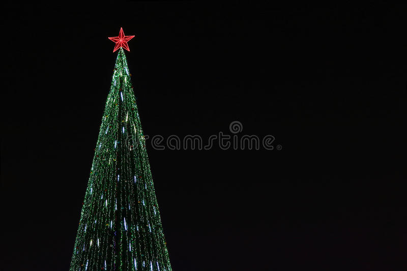 Beautiful christmas tree with bright illumination. And red star at dark night outdoor royalty free stock images