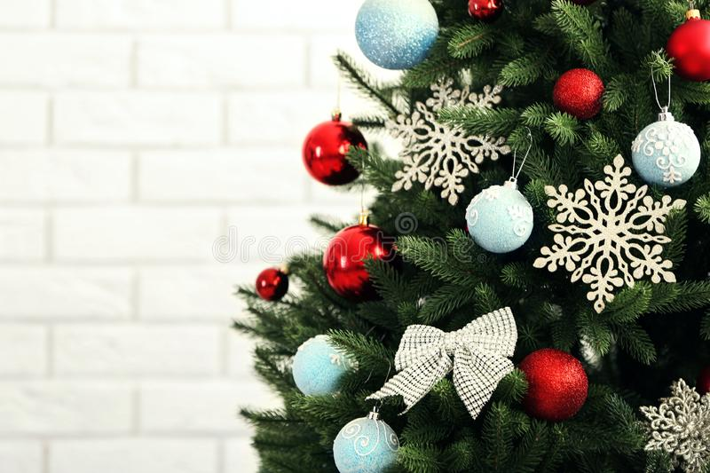 Beautiful Christmas tree with decor against wall. Space for text. Beautiful Christmas tree with decor against brick wall. Space for text royalty free stock photo