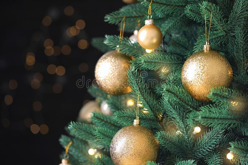 Beautiful Christmas tree with festive decor against blurred lights on background. Closeup royalty free stock photo