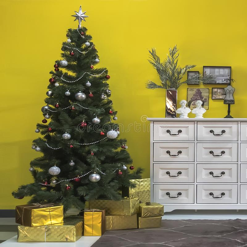 Beautiful Christmas tree with gift boxes in interior of living room stock photo