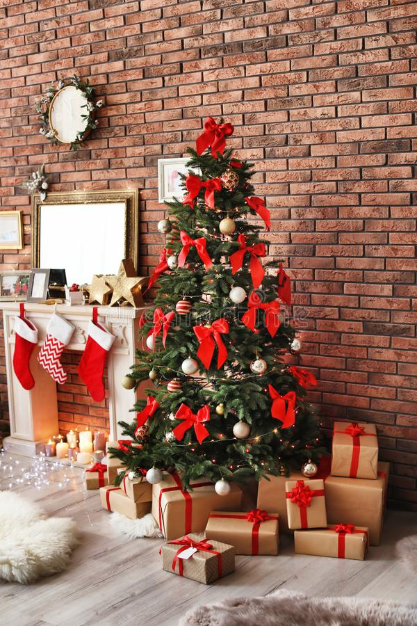 Beautiful Christmas tree and gifts near fireplace with stockings indoors stock photography