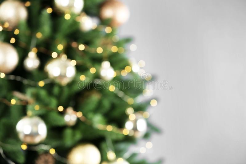 Beautiful Christmas tree with lights against grey background, blurred view. Space for text stock image