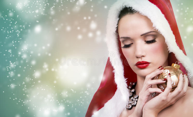 Beautiful Christmas woman. Upscale woman in Santa Claus theme outfit holding Chrsimas gold ornament on winter background with snow royalty free stock images