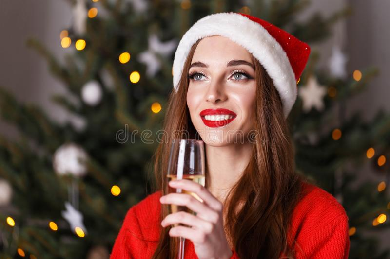 Beautiful Christmas Woman Wearing Santa Hat Drinking Champagne While Staying Near The New Year Spruce royalty free stock images
