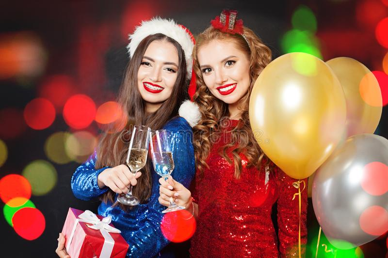 Beautiful Christmas women smiling. Winter fashion girls on abstract bokeh glitter sparkle party background stock photos