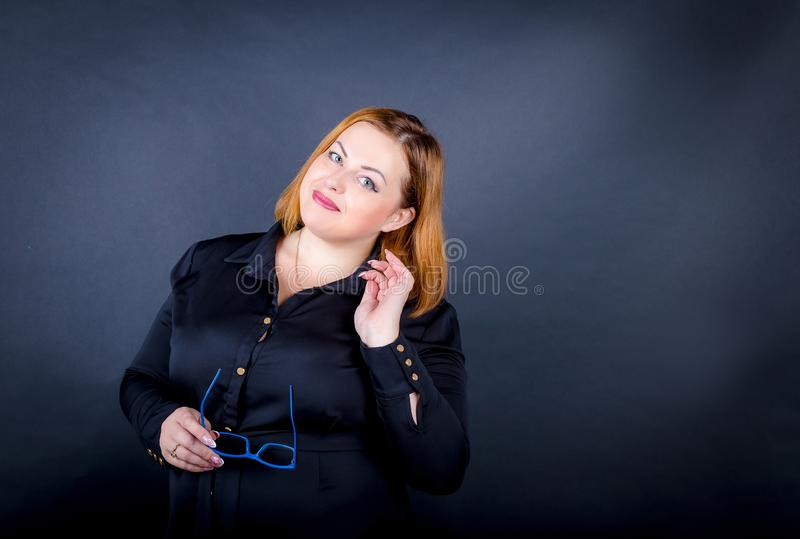 Beautiful chubby girl in a black dress on a dark background. royalty free stock photo