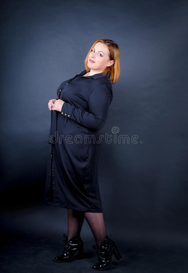 Beautiful chubby girl in a black dress on a dark background. royalty free stock images