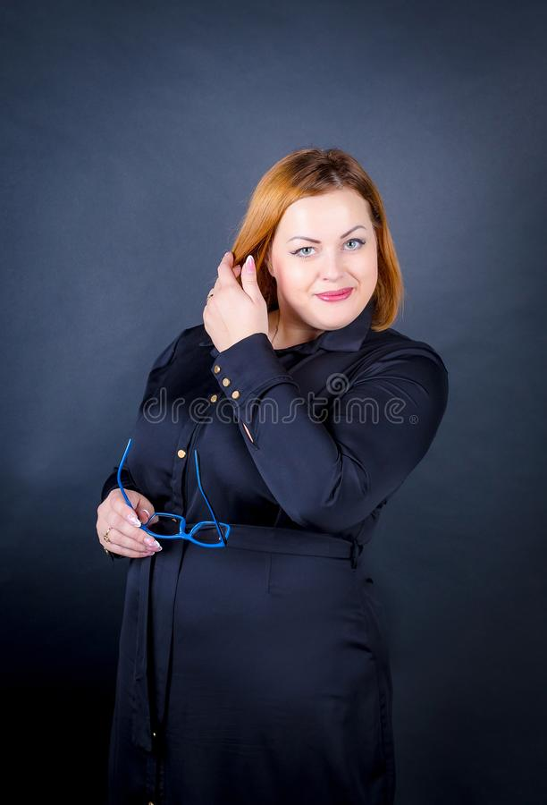Beautiful chubby girl in a black dress on a dark background. stock image