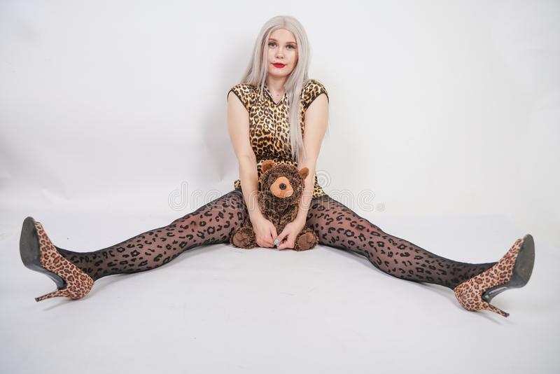 Beautiful chubby platinum blonde with red lips wearing leopard print short dress and black pantyhose on white background in Studio stock images