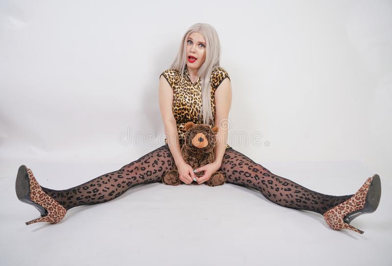 Beautiful chubby platinum blonde with red lips wearing leopard print short dress and black pantyhose on white background in Studio stock photo
