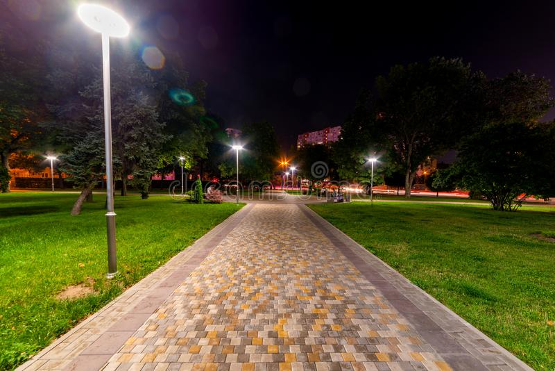 Beautiful city park walkway with lamps at night royalty free stock photo