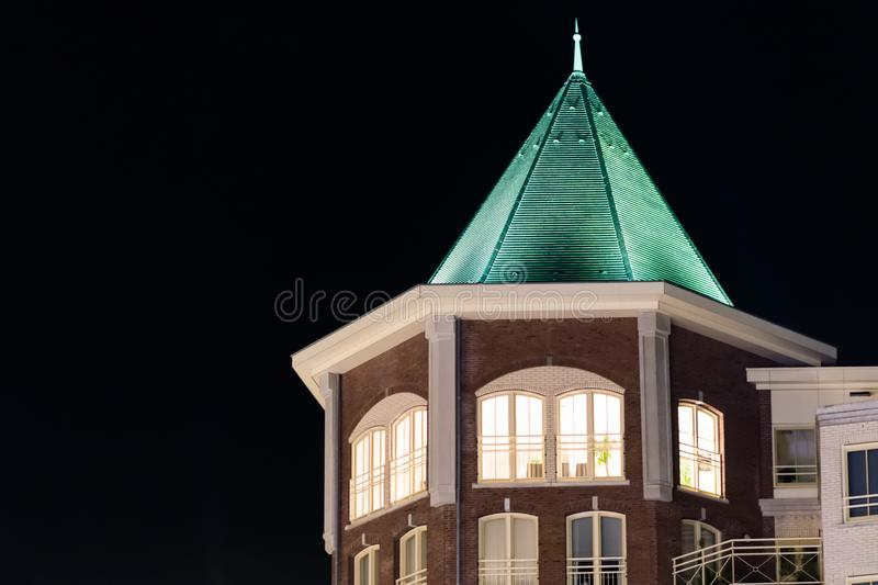 Beautiful city tower building with lighted apartment windows and a pointy rooftop, modern dutch architecture at night. A beautiful city tower building with royalty free stock photo