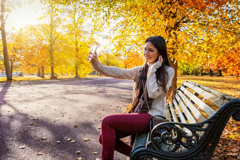 Woman sits in a park during golden autumn time and takes selfie photos royalty free stock image