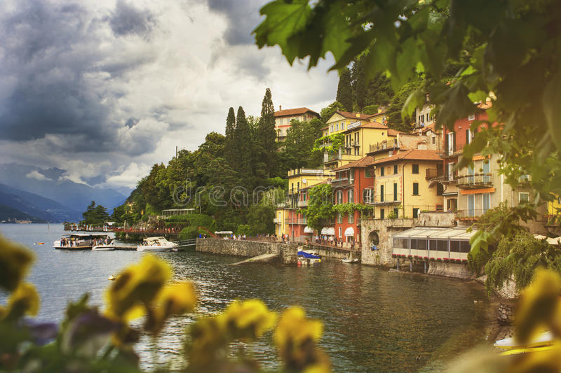 Beautiful cityscape with a Como lake coastline of italian Varenna city with colorful building, big trees, and dramatic sky. Before the rain with a bokeh flowers stock photography