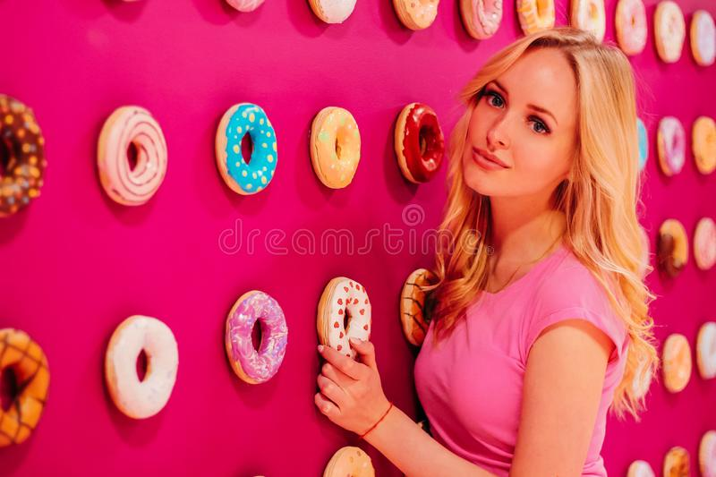 Beautiful clamour blonde girl in pink closeup on the pink donut background.  stock images