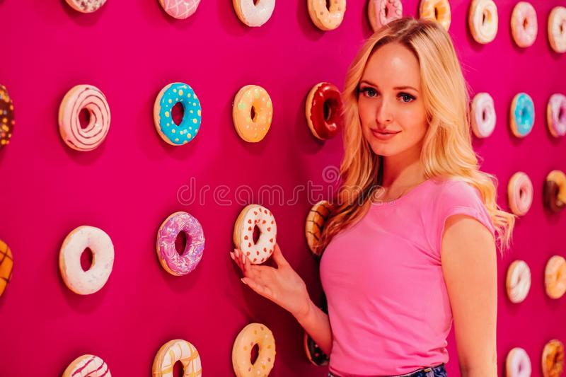 Beautiful clamour blonde girl in pink closeup on the pink donut background.  stock photography