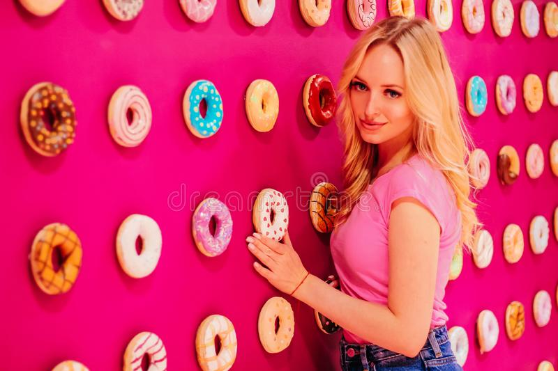 Beautiful clamour blonde girl in pink closeup on the pink donut background.  royalty free stock photos