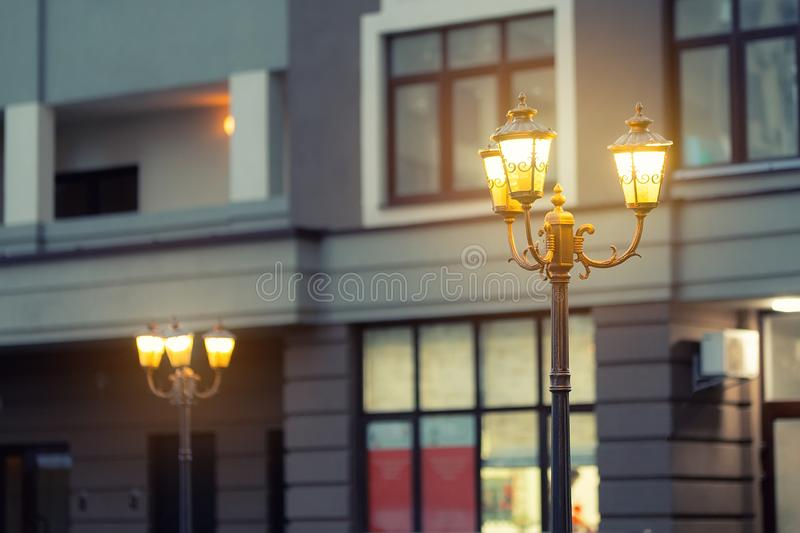 Beautiful classic metal street lamp in evening against modern building in evening. Warm light iron retro lantern at city. Street at twilight time royalty free stock photos
