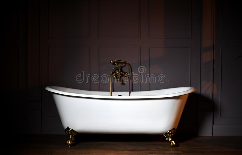 Beautiful classic style white claw foot bathtub with stainless steel old fashioned faucet and sprayer stock photos