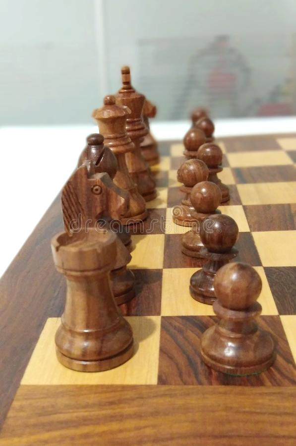 One side black chess piece on chess board ready to play. A beautiful classical wooden made chess piece and chess board royalty free stock images