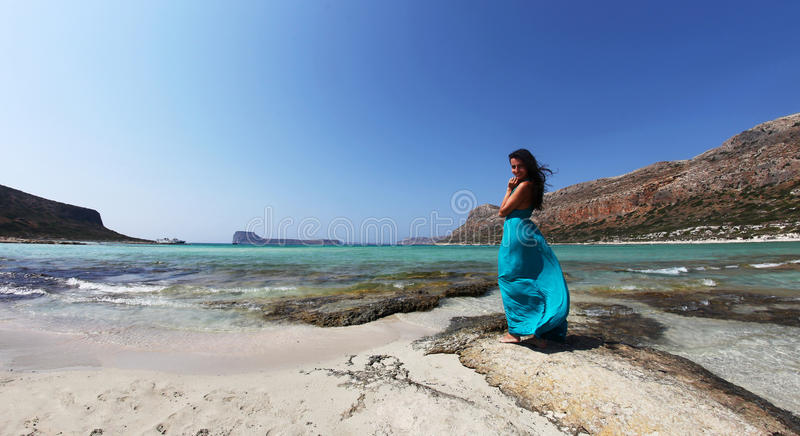 Beautiful classy woman on a beach with turquoise clear waters. A panoramic landscape from Balos Lagoon, Crete, Greece with a woman in turqoise dress near the the royalty free stock photography