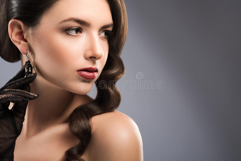Beautiful classy woman on grey background. Close up portrait of a gorgeous brunette woman with red lips posing gracefully looking away copyspace beauty makeup royalty free stock photography