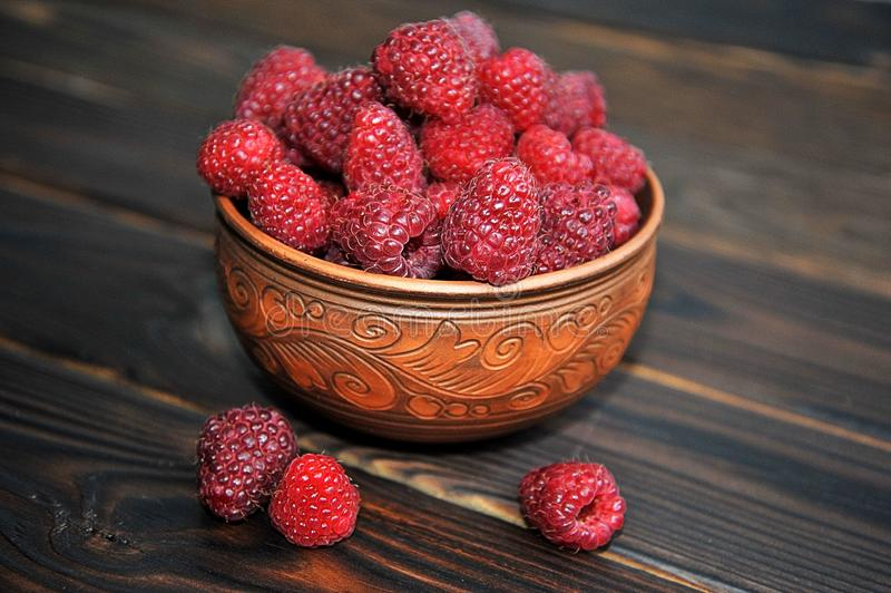 A beautiful clay pot with raspberries on a wooden table. raspberries in a plate. Side view stock photo