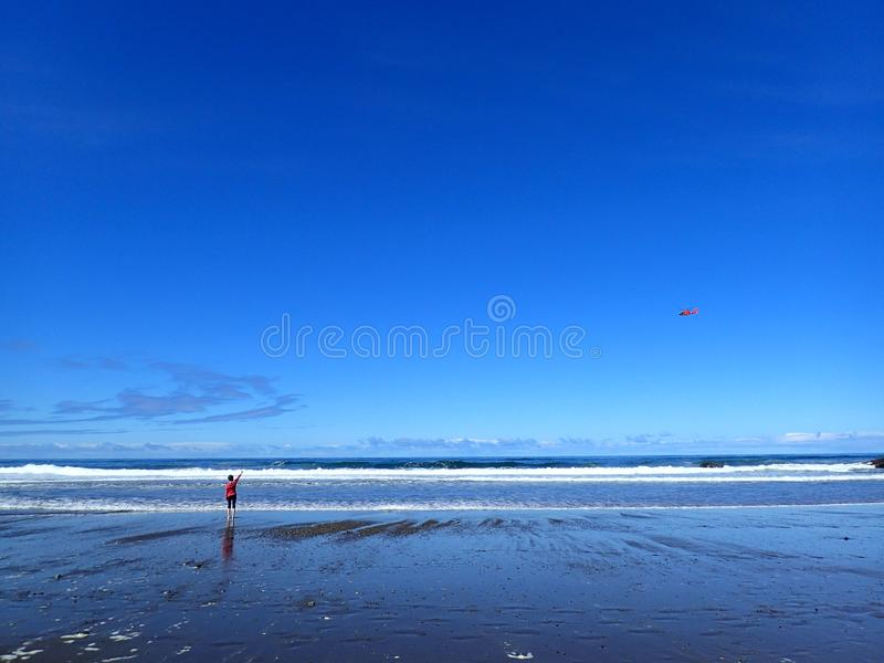 A Beautiful Clear Day at a Beach with Girl and Helicopter royalty free stock photo