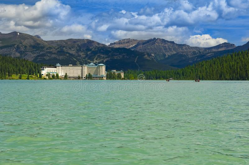 Lake Louise with famous Fairmont Chateau in sunlight,. Beautiful clear Lake Louise in Banff National Park, Alberta, Canada, and Fairmont Chateau at the shore of royalty free stock photo